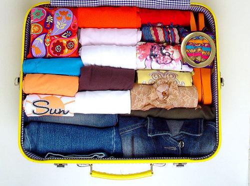 Dicas para organizar mala de viagem. Mochila amarela com roupas dobradas em forma de rolos, para caber mais peças dentro.